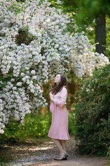リンゴ園における妊娠中の女性はおなかとリンゴの開花枝を保持しています。