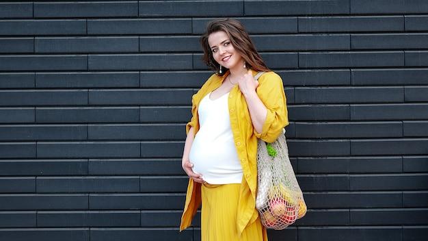 Беременная женщина в желтой одежде с эко-сумкой с фруктами и овощами на черной стене. концепция без пластика устойчивый образ жизни.