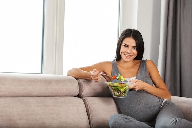 Беременная женщина в помещении дома, сидя на диване, ест салат.