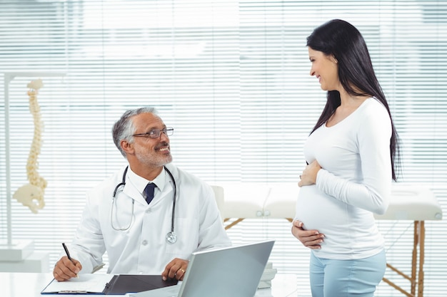 Pregnant woman interacting with doctor at clinic during health checkup