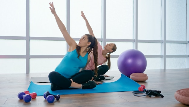 A pregnant woman is doing physical exercises for pregnant women