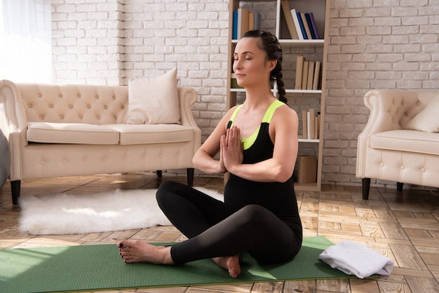 Pregnant woman is doing yoga and meditates at home