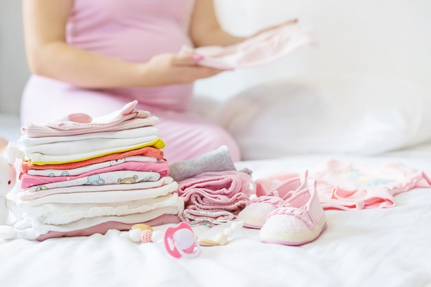 A pregnant woman is folding baby things