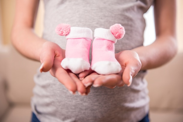 Pregnant woman is holding belly on little socks for babies.