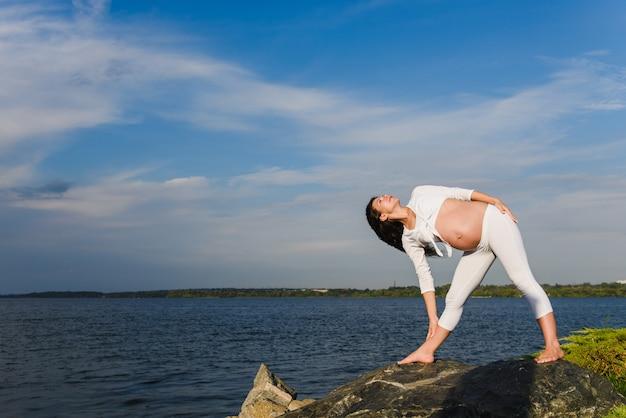 妊娠中の女性は川のそばでヨガを練習しています。