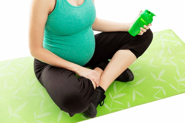 A pregnant woman is sitting on a fitness mat with a bottle of water in her hand. mother and baby health. isolated on white wall.
