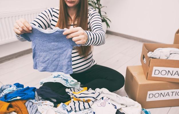 Беременная женщина разбирает детскую одежду и хочет отдать вещи на благотворительность