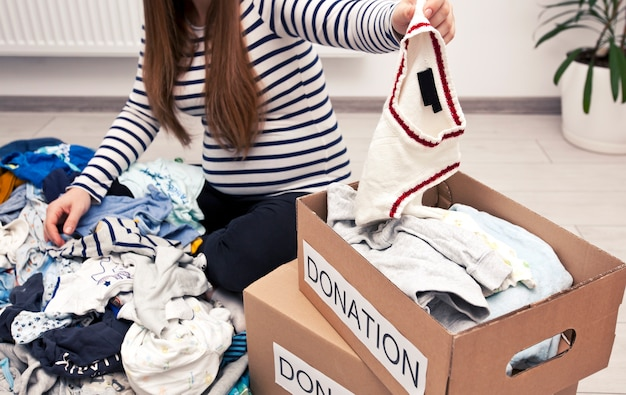 Pregnant woman is sorting baby clothes and wanna give some things to charity