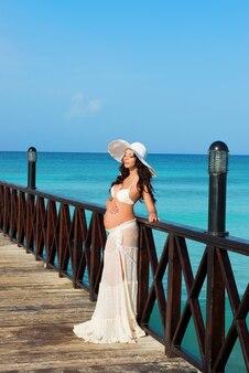 Беременная женщина стоит на деревянном пирсе на фоне моря. доминиканская республика, карибское море.