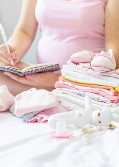 A pregnant woman is writing a list