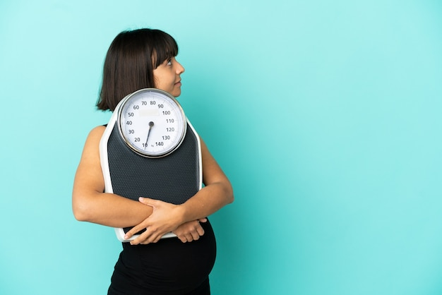 Pregnant woman over isolated background with weighing machine and looking side