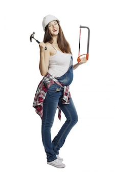 A pregnant woman in jeans with a big belly with construction tools in her hands and in a helmet.