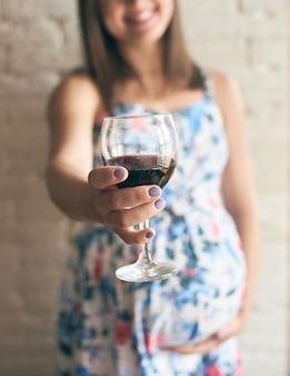 와인 잔을 유지 하 고 응원하는 임산부