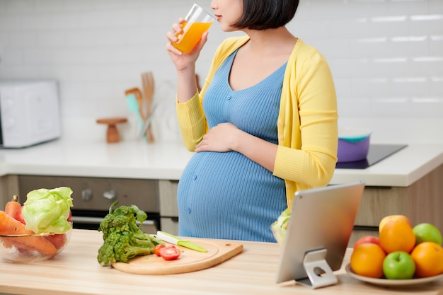 Pregnant woman on kitchen drinking healthy fruit juice
