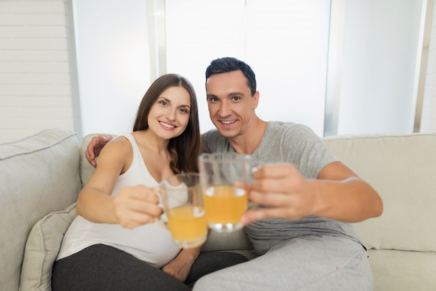Pregnant woman lies on sofa. man is sitting next to her.