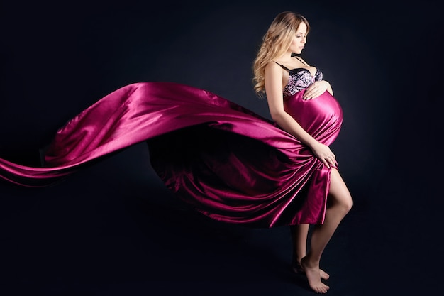 Pregnant woman in lingerie on black background