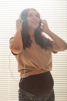 임산부는 집에서 헤드폰으로 음악을 들으며 춤을 춥니다