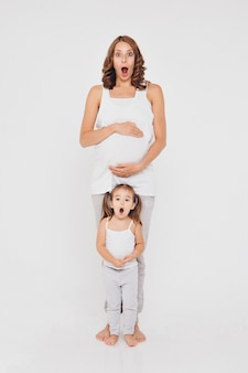 Pregnant woman and little girl in sportswear on white background. the girls holds her stomach.