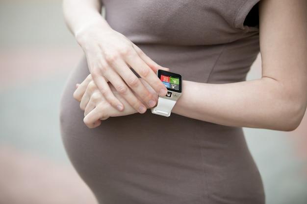 スマートウォッチを見ている妊娠中の女性。閉じる