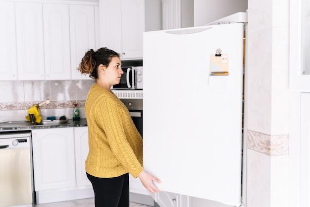 Беременная женщина смотрит в холодильник с обеспокоенным выражением