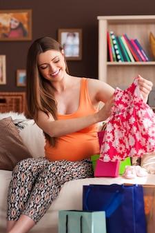 Беременная женщина смотрит на новое платье для маленькой девочки