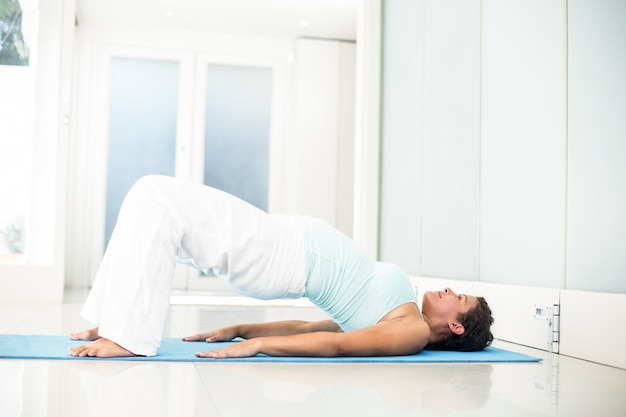 Pregnant woman lying on floor in bridge pose