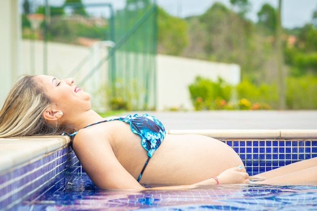Pregnant woman lying in the pool.