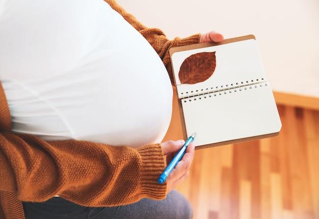 임신한 여자는 노트북에 메모를 합니다 아기의 젊은 어머니 기대