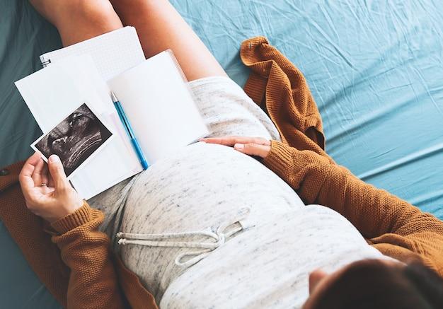 Беременная женщина делает заметки, глядя на ультразвуковое изображение и медицинские документы