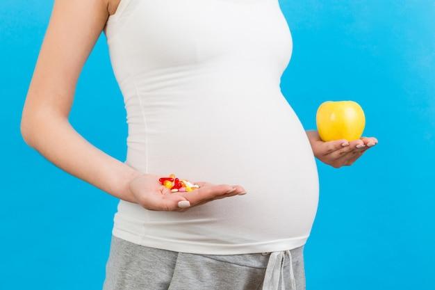 Беременная женщина делает выбор между яблоком и кучей таблеток