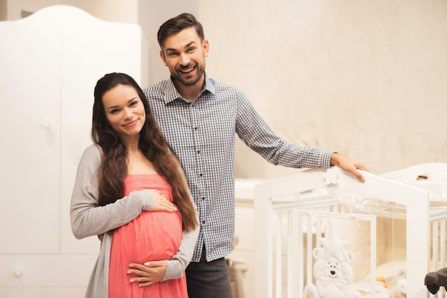 A pregnant woman and a man choose a cot.