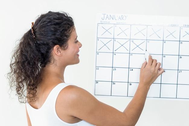 カレンダーで日付を記入している妊娠中の女性