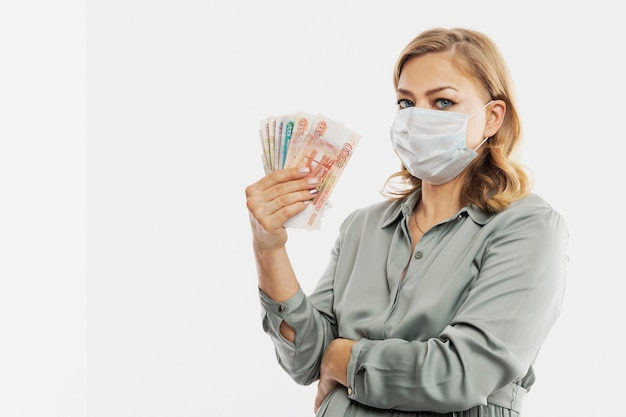 A pregnant woman in a mask holds russian banknotes in her hand. maternity capital, government assistance. space for text. white wall.