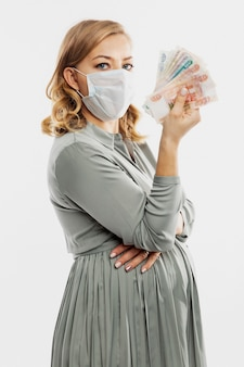 A pregnant woman in a mask holds russian banknotes in her hand. maternity capital, government assistance. white wall. vertical.