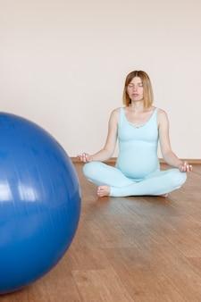 フィットネスボールとスタジオで瞑想妊娠中の女性