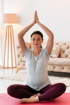 Беременная женщина медитирует в помещении