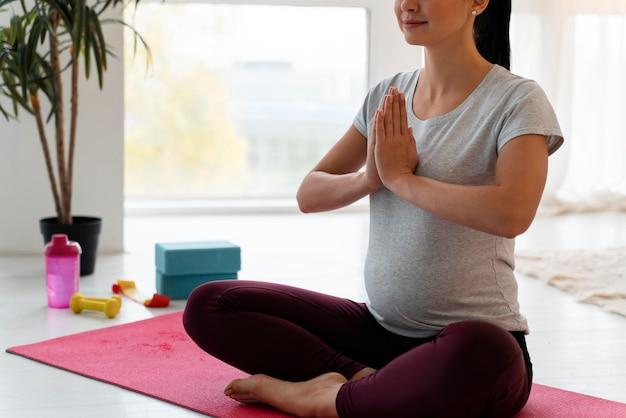 Беременная женщина медитирует на полу в помещении
