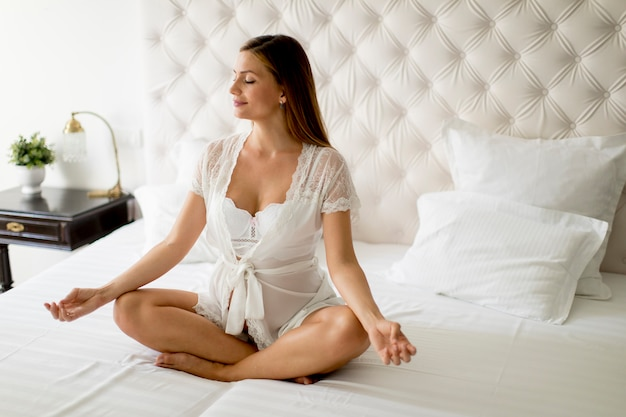 Pregnant woman meditating and practicing yoga in her bedroom