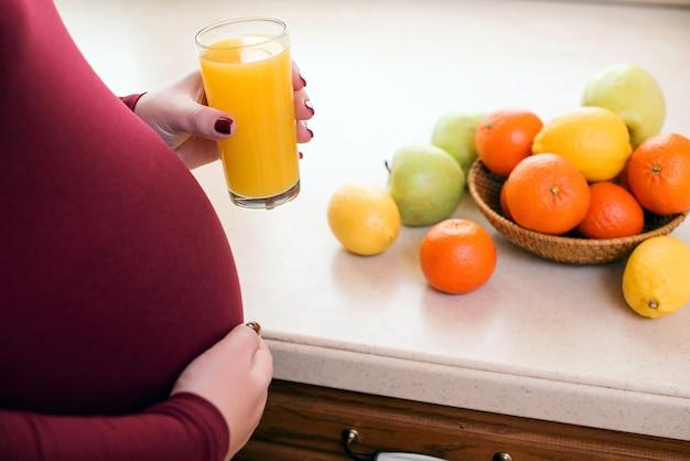 健康的な食事とキッチンで妊娠中の女性。妊娠中の健康的な栄養と食事。フレッシュジュースのガラスを持つかわいい若い妊婦。