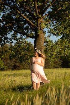 Беременная женщина на фоне поля
