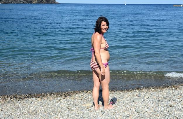 ビーチの背面図とカメラを見て妊娠中の女性