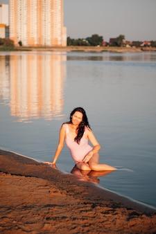 Беременная женщина на пляже милая расслабляющая молодая беременная женщина в розовом купальнике наслаждается прохладой ...