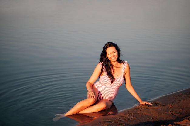 ビーチの妊婦は砂浜に座っているピンクの水着で平和なリラックスした妊婦...