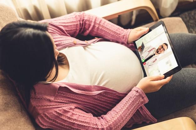Беременная женщина по видеосвязи, оставаясь дома на карантине в безопасности