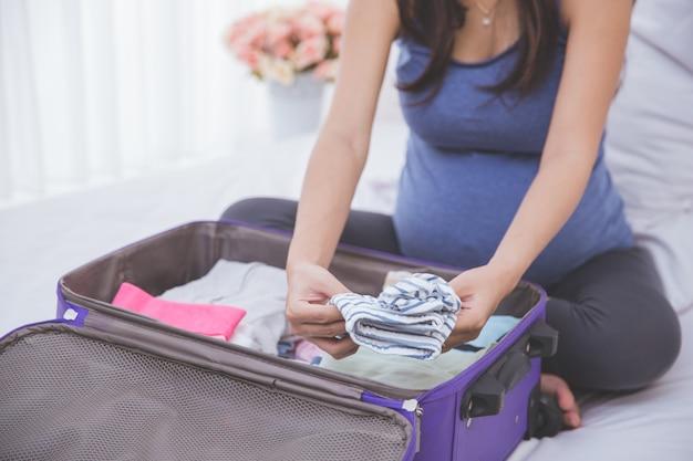 妊娠中の女性が新生児服を整理