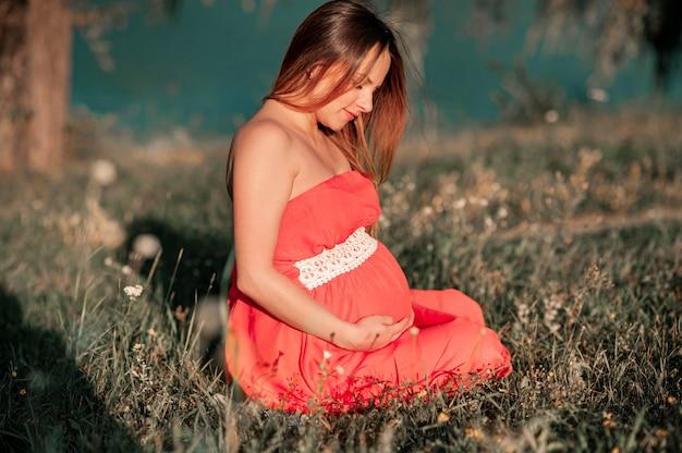 Беременная женщина на открытом воздухе с цветами на лугу.