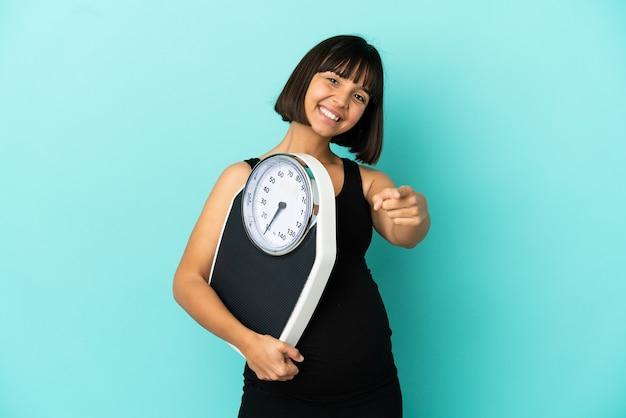 計量機を保持し、正面を指している孤立した背景上の妊娠中の女性