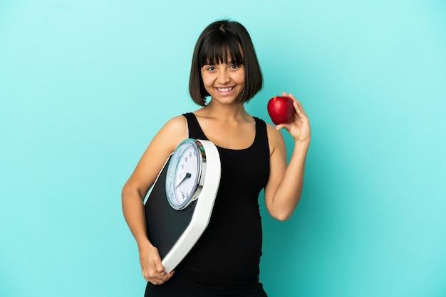 Беременная женщина на изолированном фоне с весами и яблоком