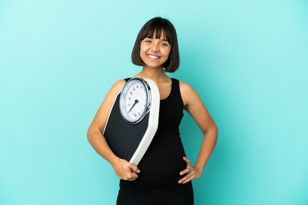 Беременная женщина на изолированном фоне с весами