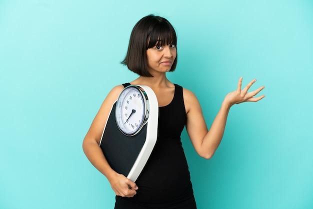 計量機で孤立した背景上の妊娠中の女性